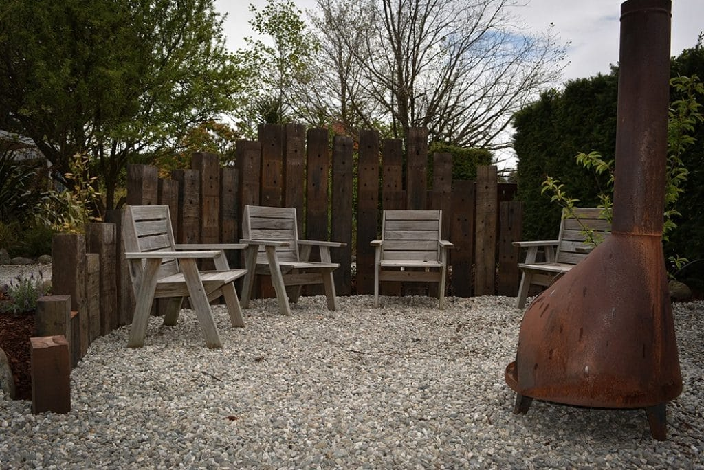 outdoor living area with seats, potbelly and vertical railway sleepers