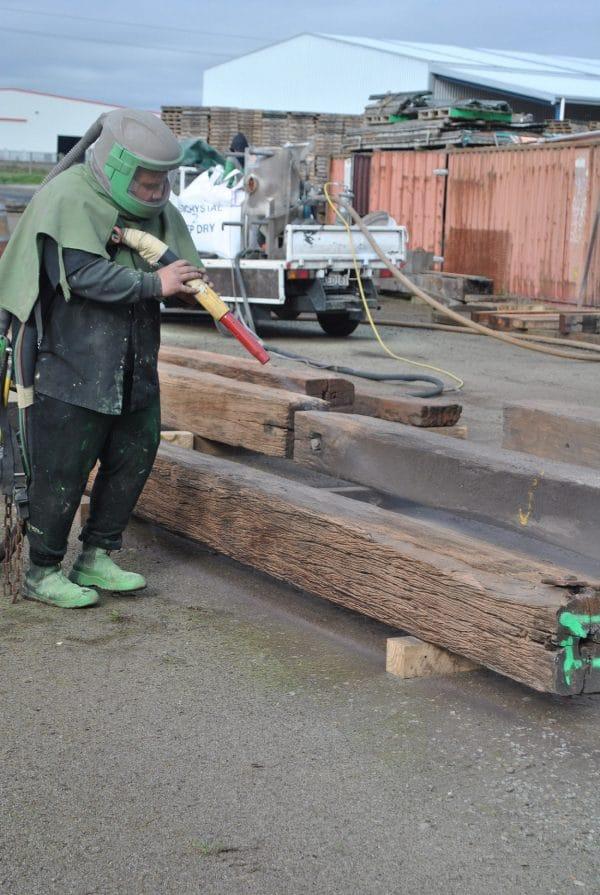 Man sand blasting rustic beam