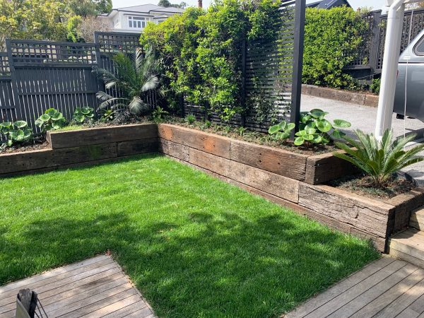 Patio with lawn and low retaining wall garden made from railway sleepers