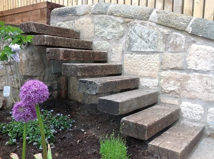 railway sleepers as floating stairway outdoor into stonewall with flowers