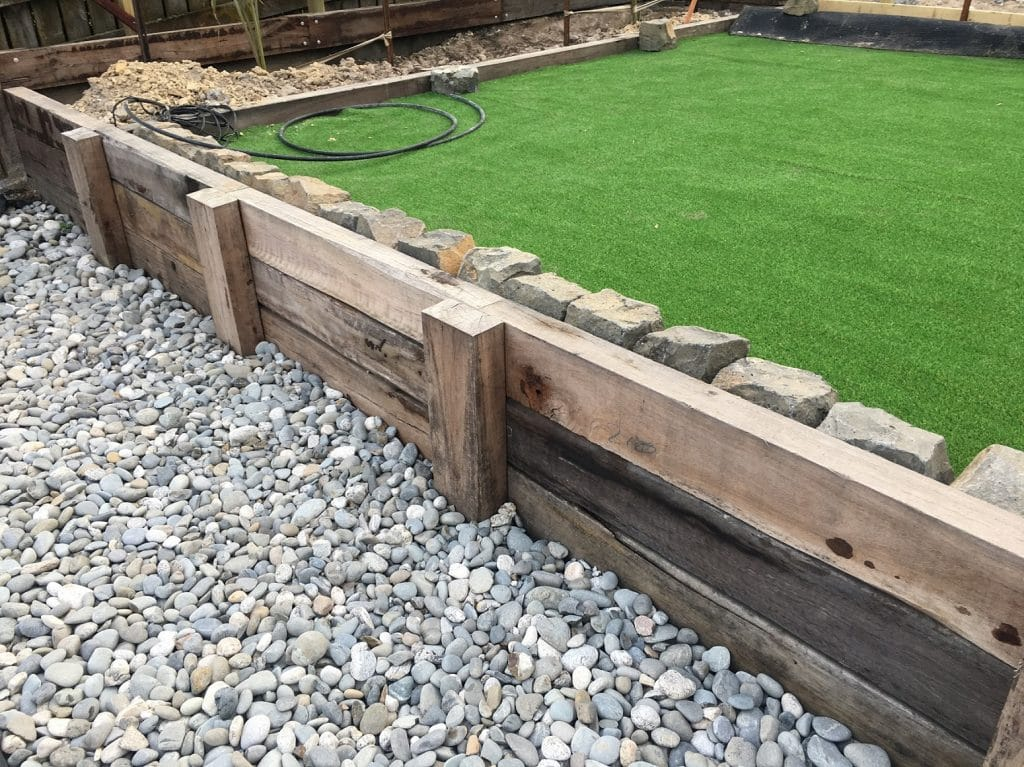 Low retaining wall made from sleepers with raised lawn in background