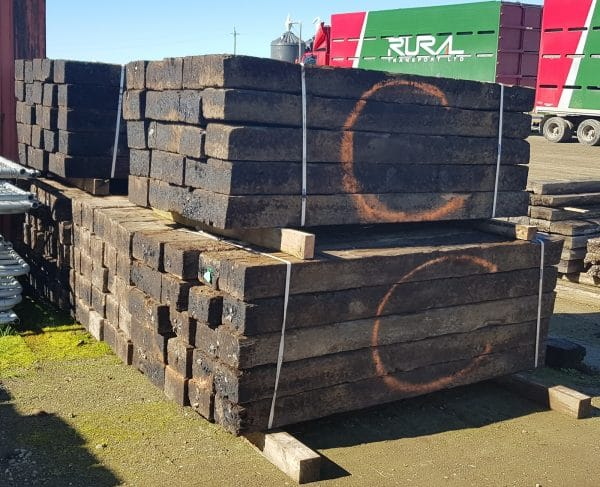 Treated railway sleepers in bundles stacked with truck in background
