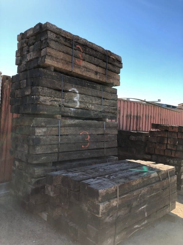 five bundles of railway sleepers stacked.