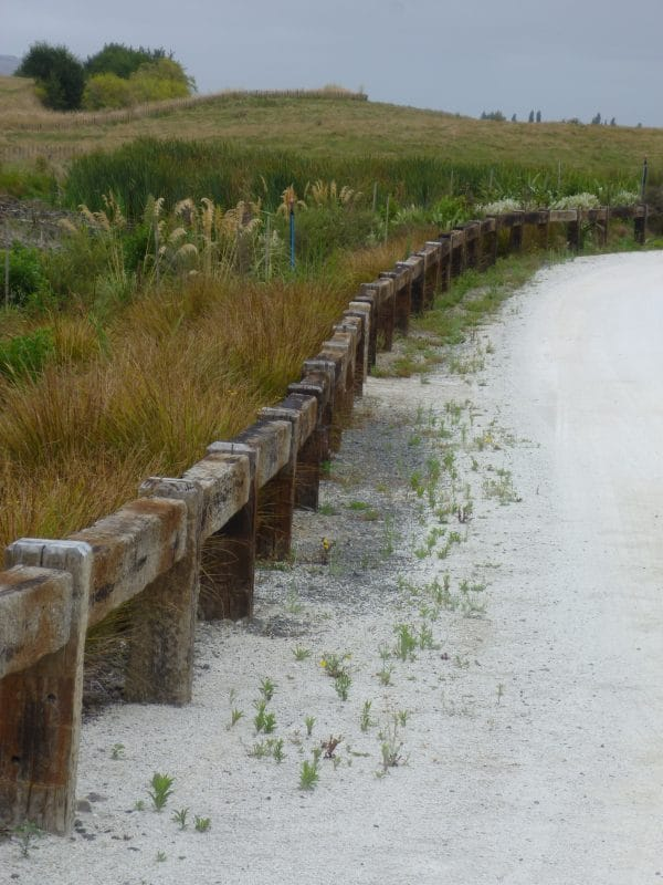 sandy path with a long low fence with shurbs