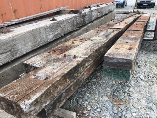 three long rustic hardwoood beams laid in storage