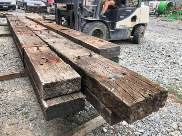 three hardwood rustic European beams with fork hoit lifting from behind